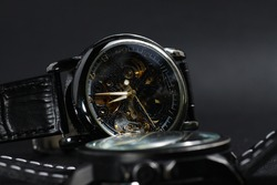 a black automatic self winding wristwatch with transparent sekeleton dial design and a black battery operated watch on black leather background