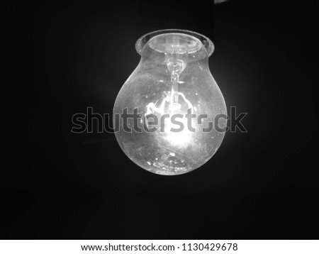 A black background glowing light bulb #1130429678