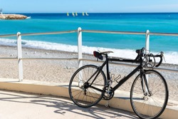 A black bicycle sits parked along a ramp to the beach as a group of matching sailboats are blurred in the distance on the French Riviera in Menton, France