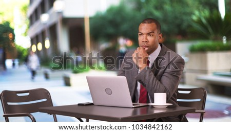 A black businessman works on his laptop while sipping coffee #1034842162