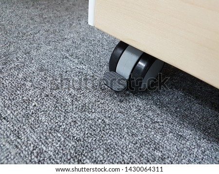 A black castor wheel of cabinet that have equipment for lock it with the floor to not move on carpet floor.