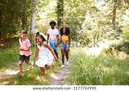 A black couple and their two kids walking in a forest