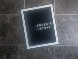 A black felt letter board with white frame is shot flat lay style on gray slate looking tile. Letters on the board are left justified and say Freebie Friday, a phrase businesses use for giveaways.