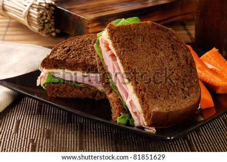 A black forest ham and swiss cheese sandwich on rye bread with carrots