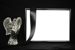 A black frame with space for text stands on a black background next to a statuette of a crystal angel and a black funeral ribbon