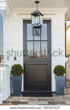 A black front door flanked by two potted plants in blue pots. The house is white. Also seen is a light fixture, off, and part of a large window. A stone porch leads to the door and doormat.