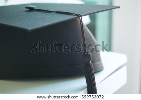 A black graduation hat on white books and background