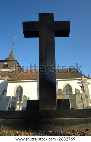 A black gravestone looms high. Behind it is the church steeple and a clear blue sky. The ghost-like reflection of a tree (new life?) can be seen in the black marble of the cross.