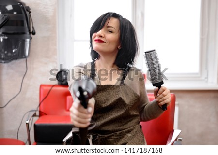 a black-haired woman hairdresser sits in a hairdresser's chair and laughs as she holds a brushing and hairdryer
