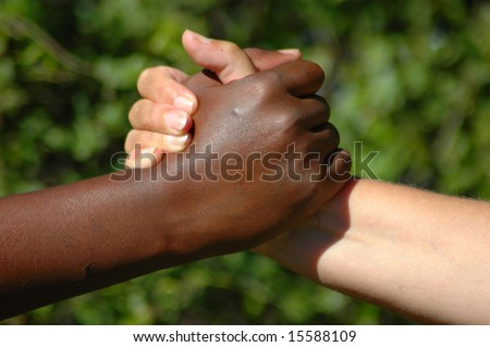 A black hand of an African American woman and a white hand of an caucasian woman holding each other to show that they are a perfect team