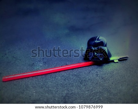 A black helmet with the light saber sword on the black background