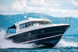 A black hull speedboat racing by sea