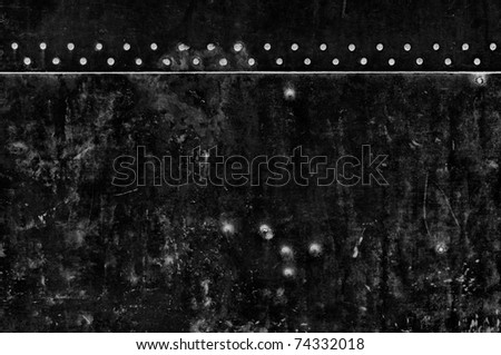 A black iron metal wall background with white rivets and grunge stains.