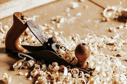A black   jack plane is on a wooden table, next to a wooden sawdust in the workshop