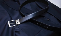 A black leather belt with steel fittings lies horizontally on a black men's jacket. An expensive gift option for men, premium leather, chic performance, handmade, exclusive. craft