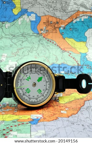 A black lensatic compass on hiking map