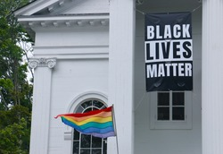 A Black Lives Matter banner and LGBT flag displayed outside a church in Lexington, Massachusetts