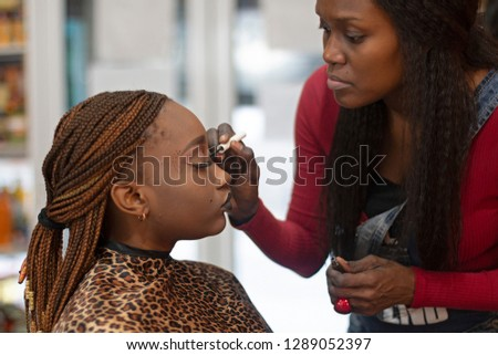 A black makeup artist apllying eyeliner on a beautiful black model.