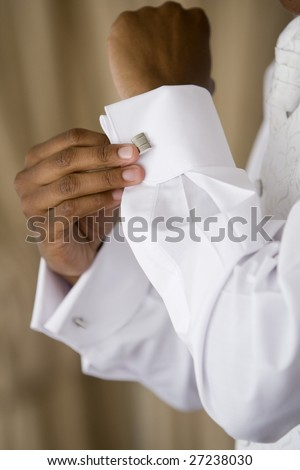 A black man fastening a cuff-link before getting married