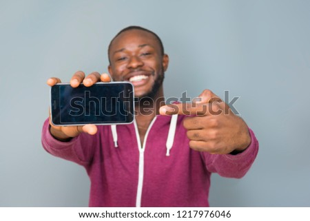 a black man smiling and stretching his phone forward showing us the screen and also pointing to it