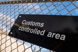 A black metal board sign with the words customs controlled area in white letters. The sign is affixed to a metal mesh wire fence. The blue sky and white fluffy clouds are in the background.
