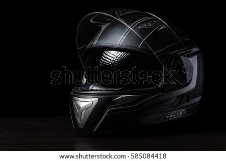 A black motorcycle helmet on dark background.
