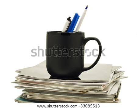A black mug holds three pens atop a stack of magazines.