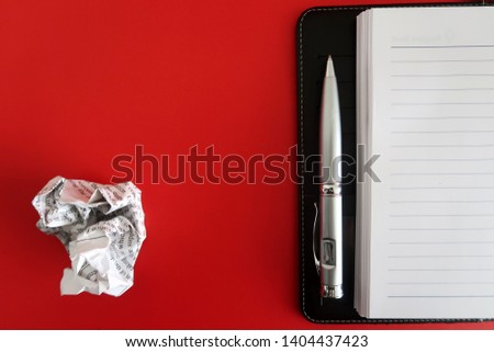 A black notebook/a pen and a crumpled paper , isolated on red background with copy space. Concept of first time writing /writers block.