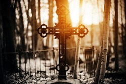 A black old patterned cross stands on a stone tombstone in the middle of the cemetery, surrounded by a dark forest, through the trunks of which the bright rays of the setting sun penetrate.