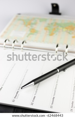 A black pen on open organizer - calendar with a world map in the background - travel plans.