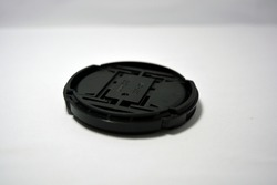 A black plastic lens cap is positioned against a white background.