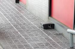 A black plastic rat trap on concrete floor. bait poison box for rat.