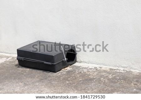 A black plastic rat trap on concrete floor. bait poison box for rat. Stock photo ©