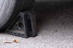 A black rubber wheel chock on the ground is placed behind a car tire to keep the vehicle in place. It is on a paved asphalt driveway with autumn leaves beside it.