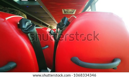 A black sefety belt with red seat on the bus.