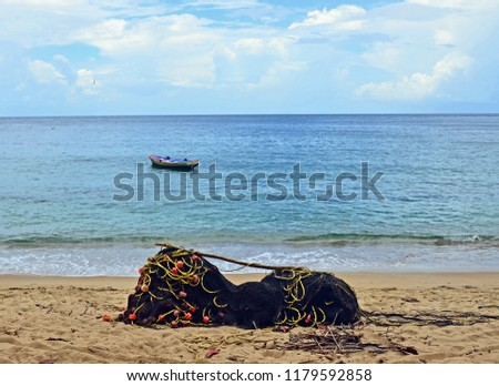 A black seine net with orange floats and yellow rope piled on a sandy Tobago beach in front of a primitive pink, yellow and blue fishing boat at anchor on calm, turquoise seas under a cloudy blue sky. #1179592858
