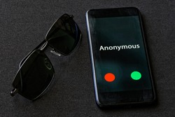 A black smartphone with an anonymous call lies on a dark fabric surface next to sunglasses. The problem of anonymity and espionage. Protection of personal information