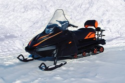 A black snowmobile with orange trim stands against a large snowdrift. Closeup, daylight, clear day. Theme of winter outdoor activities and transport rental.