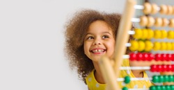 A Black student in a yellow dress laughs brightly behind a colored abacus in an elementary school classroom