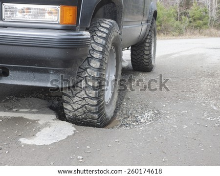A black SUV with a front wheel sunk in a water filled pothole on an old rural asphalt/dirt road #260174618