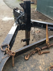 A black trailer hookup with large chains, screws, and a yellow lever. Below the triangle shape is a a dangling cable and the dirt ground.