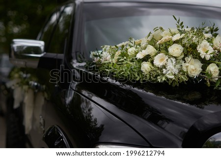 A black wedding car decorated with white roses, bridal bouquet, just married Foto stock ©