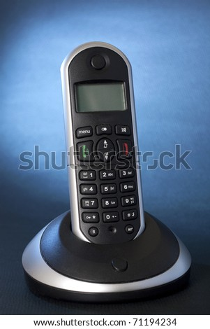 A black wireless telephone on a cradle, background focus with  blue gel