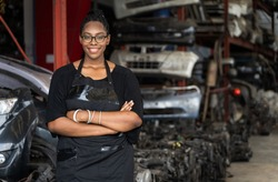 A black woman who owns a business stands with arms folded, smiling and looking at the camera on blur factory background. A black worker stands at the auto parts factory in Business onwner concept