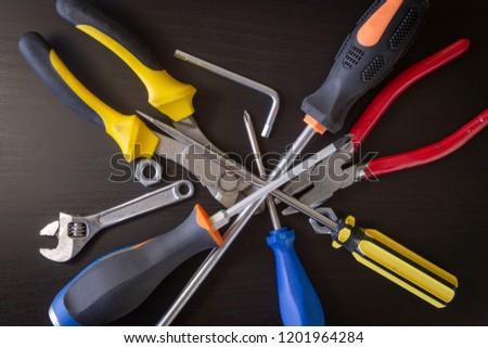 A black wooden background with various hardware tools: wrench, hexa key, nut, cutting pliers, pliers, screwdriver.