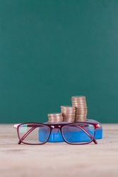 A blackboard eraser with a stack of dollar coins and a pair of glasses in front of a blackboard background