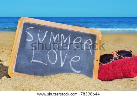 a blackboard with sentence summer love written on it, at towel and sunglasses on the beach