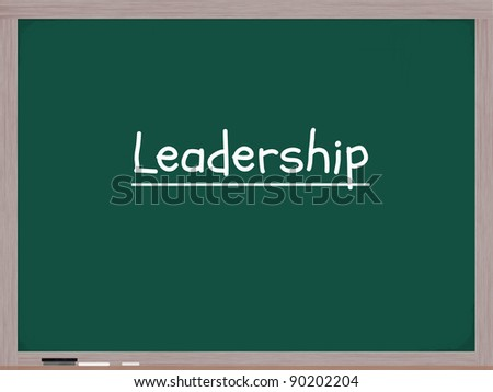 A blackboard with the word Leadership written on it in white chalk with an eraser on the bottom.