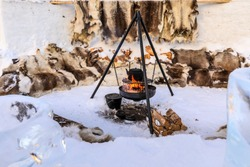 A blackened metal kettle on a cooking tripod boiling over a flaming fire, outdoors in the snow, surrounded by seats covered in reindeer skins, Arctic Circle, Alta, Troms og Finnmark, Northern Norway