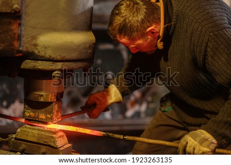 A blacksmith forging a red-hot iron billet on an automatic wall. Handicraft concept Stock fotó ©